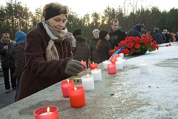 Deelnemers van de reis leggen bloemen en steken kaarsjes aan op de asheuvel van Sobibor